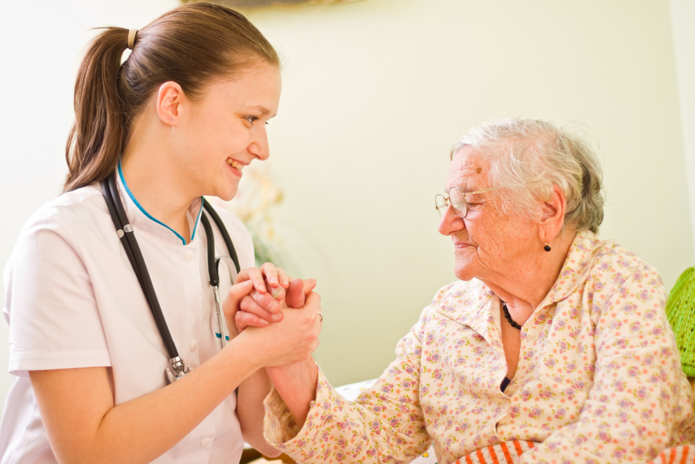 A young doctor / nurse visiting an elderly sick woman socialising - talking - with her, holding her hands.
