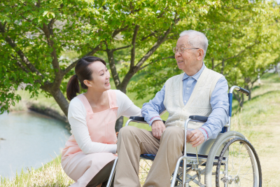 caregiver and senior smile in the field