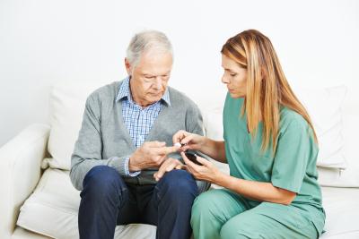 nurse monitoring blood glucose of senior men